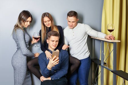 Young men and women are viewing photos from a student party on screen of a cell phone or smartphone. College students communicate in a dorm room, watch videos on a mobile device and drink alcohol.