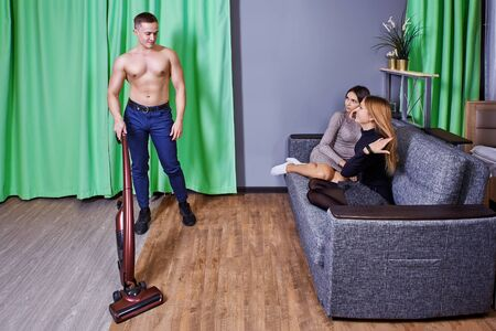 A young Caucasian male with an athletic build entertains women at a slumber or hen party. Standard-Bild