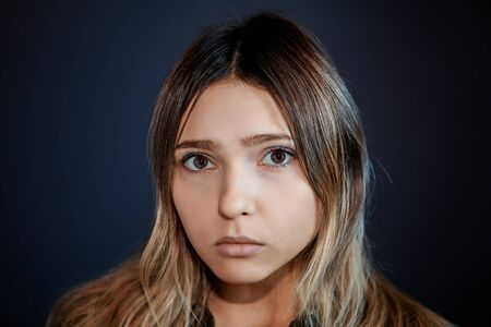 Offended expression on the face of a young woman with brown eyes and long hair. Stock Photo