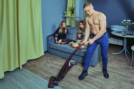 Cleaner stripper at a bachelorette party in residence hall. A young muscular man entertains women with striptease, playing the role of a maid. White male vacuuming the floor using a vacuum cleaner.