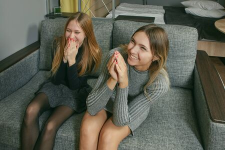 Two slender young women of Caucasian ethnicity are laughing while sitting on a sofa indoors. Cute white girls having fun in a dorm room or apartment. Females are 22 years old happy.