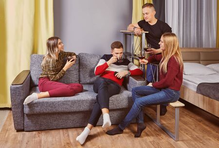 Students drinking alcohol in university dormitory. Campus housing, living on residence hall, residential life in college dorm. Young men and women drink wine in the bedroom. Party with spirits.
