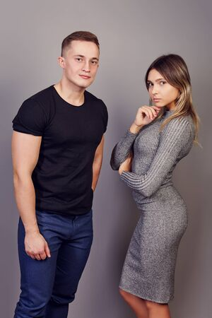 A graceful slender woman in a tight-fitting knitted gray dress stands next to a pumped-up white man in a black T-shirt. Young Caucasian female and male 22 years old, posing for a photographer standing 写真素材