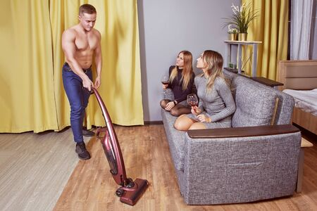 Two young women are sitting on couch with glasses of alcohol in their hands and watching a muscular shirtless man vacuuming floor of an apartment using a cordless vacuum cleaner or electric broom. Stock Photo