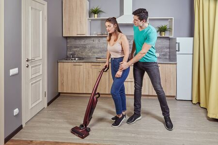 Sexual harassment, discrimination and sexism in workplace. Employer violence over employee A white man pestering a beautiful young maid woman who is vacuuming kitchen floor using a vacuum cleaner.