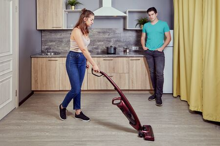 Sexual discrimination against women in the family. A young white female vacuums the kitchen floor using a wireless vacuum cleaner, while a Caucasian male watches his wife work. Home sexism.