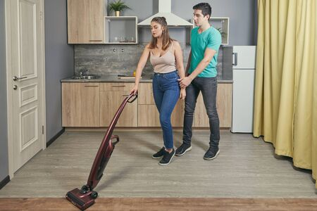 Two newlyweds had a fight. Young white man and woman in a quarrel. A 22 year old Caucasian female was offended by her male. Girl vacuums floor in kitchen, and her boyfriend distracts her from work. Banco de Imagens