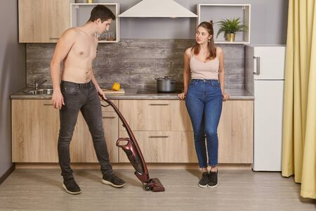 A young Caucasian woman is flirting with a white shirtless man who is cleaning the kitchen in a university dormitory using a wireless upright vacuum cleaner or electric broom. Banque d'images