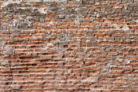 Surface texture of an old crumbling red brick wall. Stock Photo