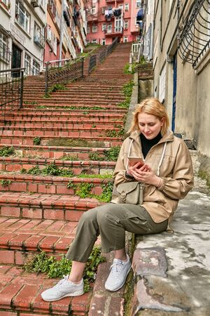A young Caucasian woman travels around Istanbul, she looks at a map in a mobile phone to navigate the terrain. White female in warm clothes makes a trip in the winter.