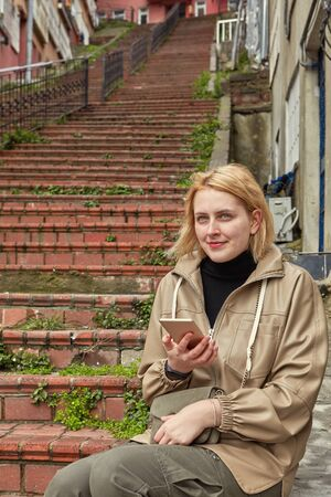 A young Caucasian woman walks alone in deserted Istanbul in winter, she is dressed in warm clothes and resting, studying the map in her smartphone, against background of a large red stone staircase.