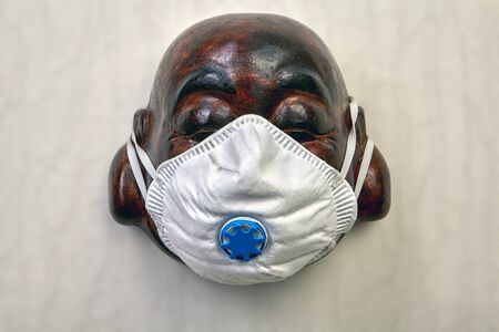 N95 respirator or facemask used to protect against covid-19 is put on a mask of a laughing Buddha purchased in a souvenir shop Stock Photo