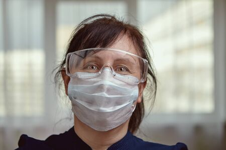 A middle-aged Caucasian woman uses personal protective equipment for self-isolation at home, so as not to get infected from sick relatives during the quarantine due to covid-19.