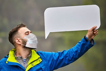 A bearded young man wearing a protective medical mask holds in his hand an empty cardboard sheet on a blurred natural background. A white male wears a facemask and shows an advertising form.