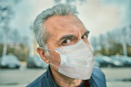 Portrait d'un homme mûr caucasien blanc dans un masque chirurgical facial protecteur jetable, qui marche dans la rue en période de pandémie de coronavirus covid-19.