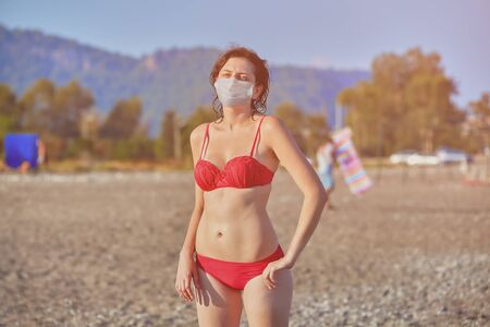 Tourism at the sea at summer 2020. Beach vacation for young pretty woman in swimsuit, who is taking sunbath on the beach with facial medical mask as a protection from covid-19 infection.