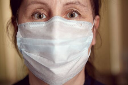 Stay at home order in light of COVID-19 pandemic. White woman in face disposable medical mask as a protection from infection during self-isolation at the resident.