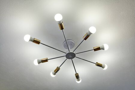 Aluminum ceiling chandelier with eight beams, at the end of which are of LED light bulbs. Economical home lighting.