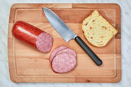 Sausage is cut into slices on a wooden beech cutting board, and lies next to a kitchen knife and a piece of bread. A meat appetizer on a marble countertop.