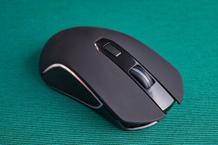 Wireless gaming computer mouse in black, with led light on green background. Battery powered input device to control the cursor on the PC screen. Stockfoto