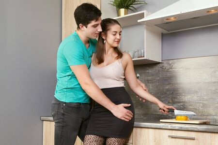 Caucasian married couple preparing food in the kitchen. Young white man and woman are hugging near the table. Lovers cooking. A guy hugs his girlfriend when she cuts vegetables.
