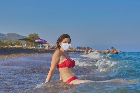 Tourist resort in summer of 2020, vacation at sea during covid-19 pandemic, an attractive young woman in surgical mask lies on sand in surf. Caucasian girl bathes with medical facemask on her face.