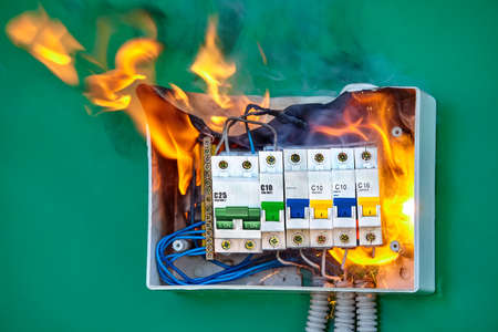 A short circuit caused an electric fire. Faulty wires led to overload of the electrical network and ignition. The distribution board in the house ignited. Burning switchboard in home.