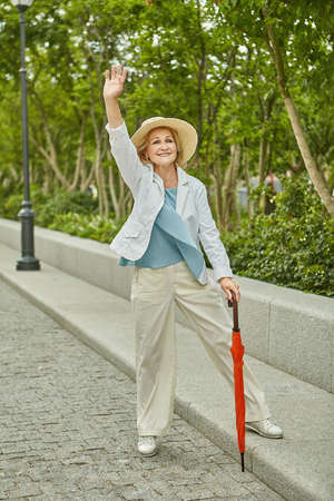 Aged white caucasian pretty traveling woman in casual cloth is standing near the road and waving a hand and smiling. She is active and cheerful.