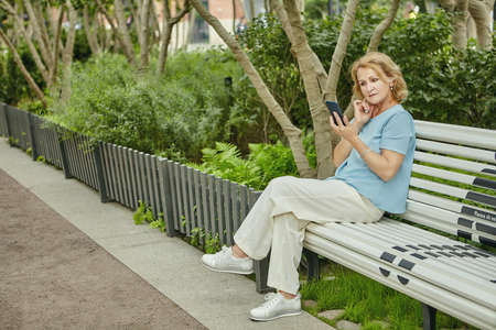 Elderly pretty white woman about 62 years old is sitting on the bench in public park and looking in her cellphone. She looks elegant in her casual clothes.