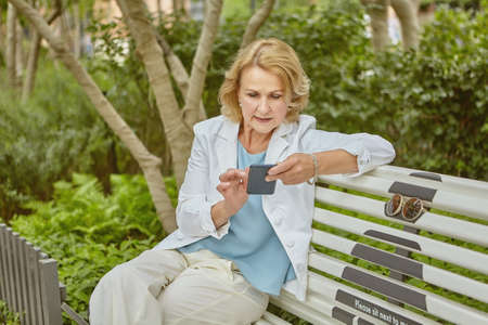 Elderly caucasian attractive woman about 60 years old is sitting on the bench in public park with smartphone in hands in the daytime. She is in casual cloth.