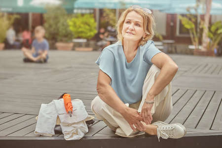 Senior caucasian white lady about 62 years old is resting in the public park. Aged acrive and cheerful woman in elegant and casual cloth is sitting outdoor.