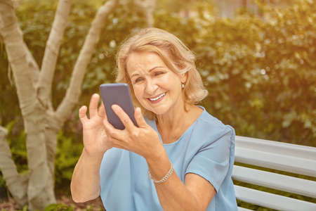 Aged attractive caucasian lady about 60 years old is using her smartphone and smiling while sitting on the bench in public park. She is active and cheerful woman in fashionable cloth.