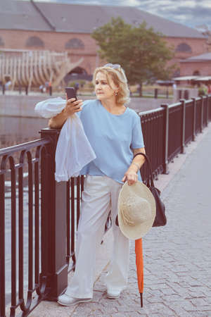 Elderly white attractive lady 60 years old is walking in the public park with mobile phone in her hands. She wears elegant casual cloth, hat and holds orange umbrella. Фото со стока