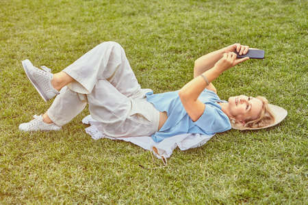Aged attractive white woman about 62 years old in casual elegant cloth is lying down the grass in the public park in the daytime with cell phone in her hands. She is smiling.