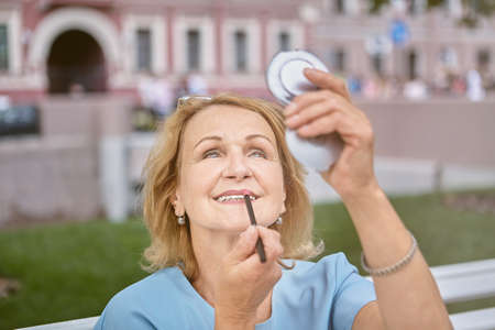 Senior caucasian white attractive lady about 60 years old is walking in downtown area and fixing makeup with a pocket mirror. She is active, cheerful and charming woman.