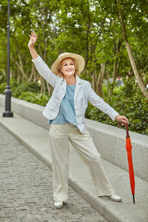 Beautiful active senior caucasian lady about 60 years old is traveling in public park at the daytime. Pretty mature businesswoman in casual and elegant cloth with hat and umbrella outdoor.