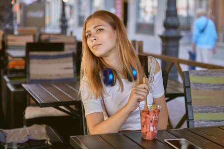 Young attractive white caucasian girl about 25 years old with blond and long hair and earphones is sitting in the street cafe and eating dessert with fruits at the daytime.