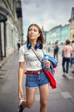 Young woman dressed in street style walks along the avenue of a European city in a crowd of people. A white female in denim shorts walking in the center of the metropolis.