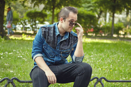 Young white man in sunglasses is sitting in the public park at the daytime. Caucasian male is walking outdoors.
