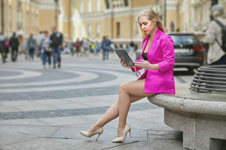 Woman in pink suit is using laptop while sitting on the crowded pedestrian street in the center of european city. Middle aged female has a trip over Russia.