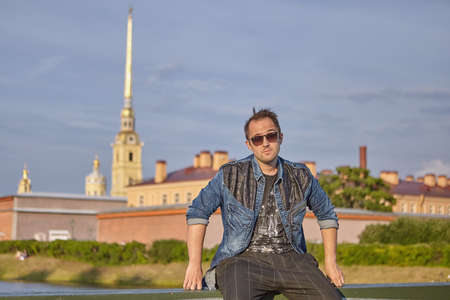 Young man in sunglasses is traveling over Saint-Petersburg, Russia. Caucasian male traveler 27 years old.