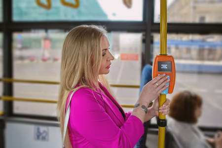 Woman is using contactless payment terminal for payment of fares in city public transport. On the display of the device an inscription in Russian