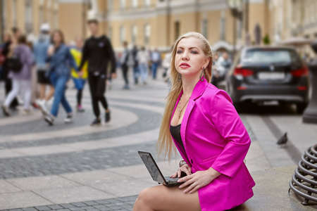 Woman in pink is using a laptop while sitting on a crowded street. Middle aged female with notebook on her knees.