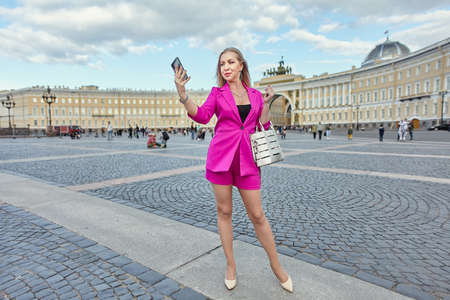Woman in pink suit is taking selfie by smartphone on the background of historic center of Saint-Petersburg, Russia.