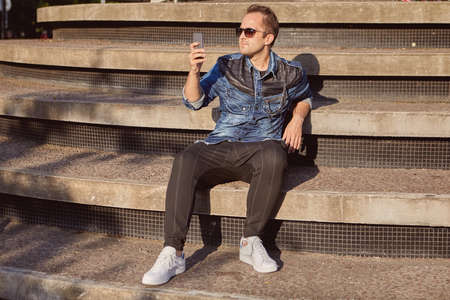 A young Russian man reads messages on a smartphone screen while sitting on the steps of a concrete staircase on a sunny summer evening. Male 27 years old uses the phone for chatting outdoors.
