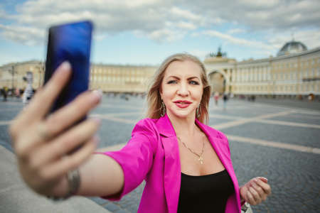 Russian woman 37 years old takes a selfie in St. Petersburg, Russia. Smiling female tourist in pink takes pictures of herself using a smartphone.