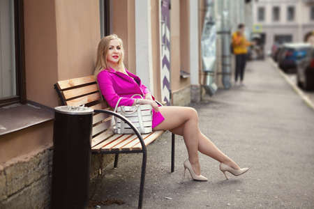 A middle-aged Russian woman, dressed in pink clothes and stiletto heels, sits on a bench in a smoking area on the street of a European city.