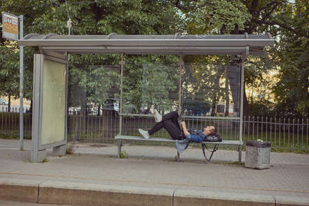 A white man at the bus stop lay down on a bench with a laptop on his knees. A young male uses a notebook computer while waiting for public transport.