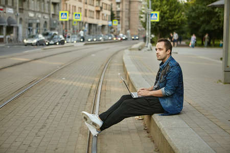 A man with a laptop is waiting for a tramway at a tram stop. Dangerous behavior on the railway, the male is resting, sitting on the sidewalk near the tracks.
