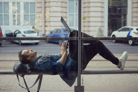 A young Caucasian man at a bus stop lies on a bench with a laptop on his lap. A white male uses a notebook computer while waiting for public transport. Zdjęcie Seryjne